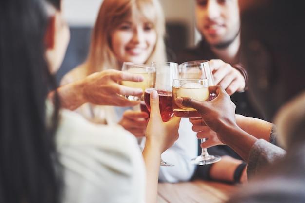 Manos de personas con copas de whisky o vino, celebrando y brindando