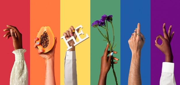 Manos de personas fluidas de género sobre fondo de arco iris