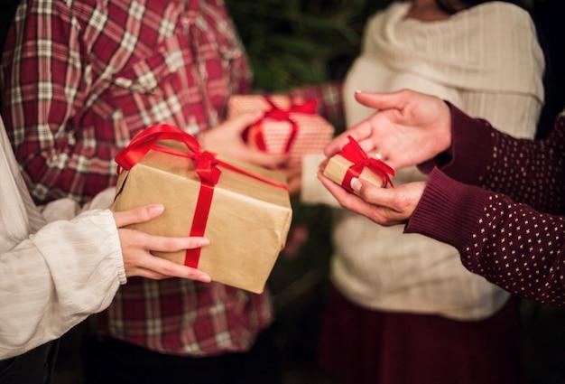 Manos de personas intercambiando regalos por navidad.