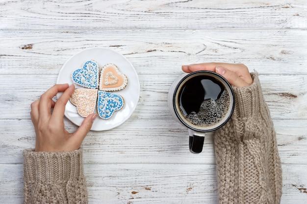 Manos de personas que muestran galletas con forma de corazón con taza de café