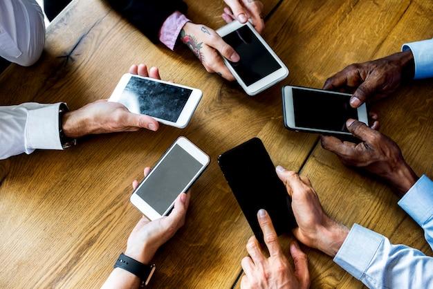 Manos de personas que usan un dispositivo de teléfono inteligente en una reunión