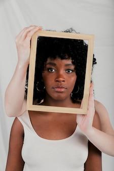 Manos de piel clara de mujer que sostienen un marco de borde de madera frente a una mujer africana