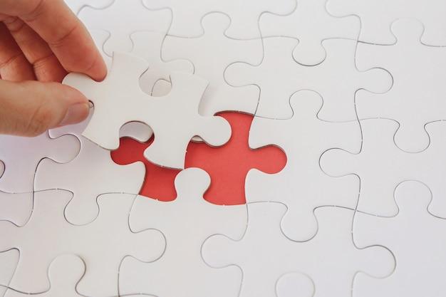 Manos con piezas de rompecabezas, planificación de estrategia empresarial