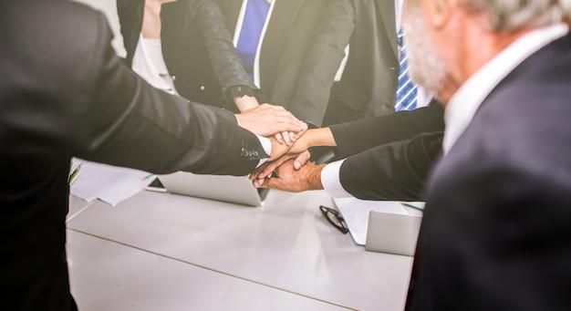 Las manos de la pila del equipo del negocio apoyan concepto en oficina