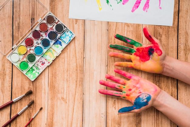 Manos pintadas con paleta de acuarela; pinceles y papel sobre mesa de madera.