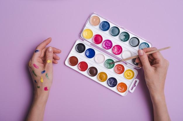 Manos pintadas con paleta de pinturas de acuarela y pincel sobre fondo púrpura, pensamiento creativo, nuevo concepto de creatividad, vista superior