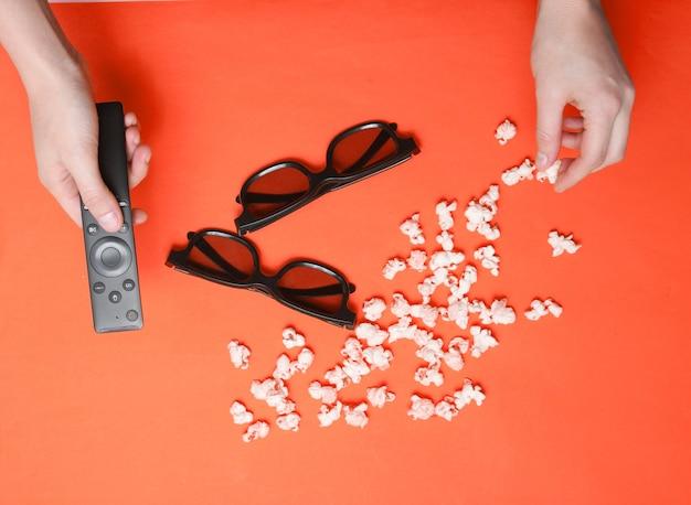 Manos planas de estilo laico con control remoto de tv, palomitas de maíz y dos pares de gafas 3d