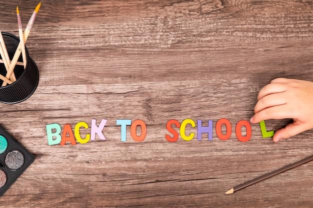 Las manos planas del muchacho de la visión superior juegan el alfabeto de nuevo a escuela en fondo de madera con el espacio de la copia