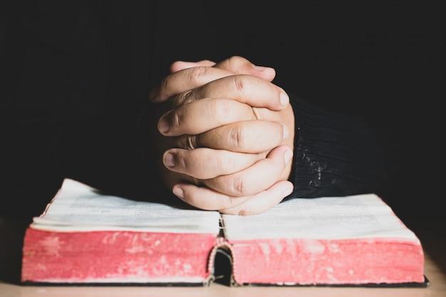 Manos plegadas en oración en una santa biblia en el concepto de iglesia por fe, espiritualidad y religión
