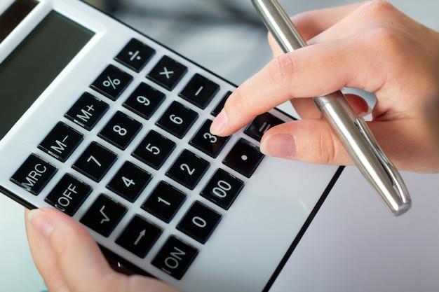 Manos con la pluma y la calculadora