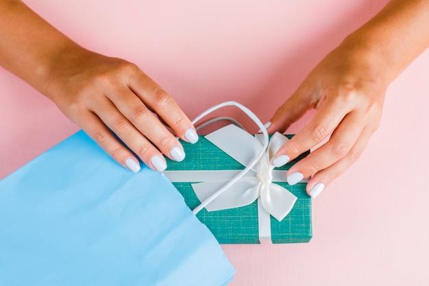 Manos poniendo caja de regalo en bolsa de papel