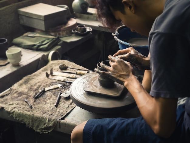 Las manos de potter formando arcilla suave para hacer una olla de barro