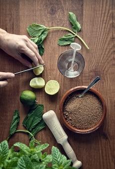 Manos preparando mojito coctel con limas y menta.