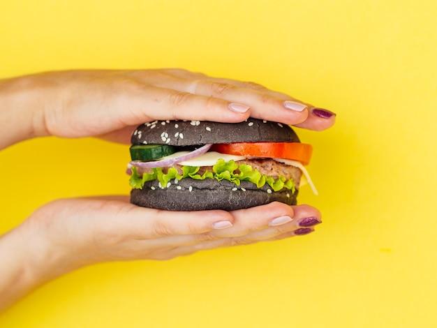 Manos presionando sabrosa hamburguesa con fondo amarillo