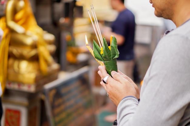 Manos del primer y de la cosecha del hombre joven asiático que sostiene un cono del incienso y de la flor