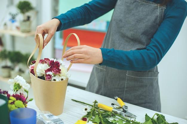 Manos del primer del florista con las flores. florista que sostiene el ramo floreciente de tulipanes rosados en un fondo de lino.