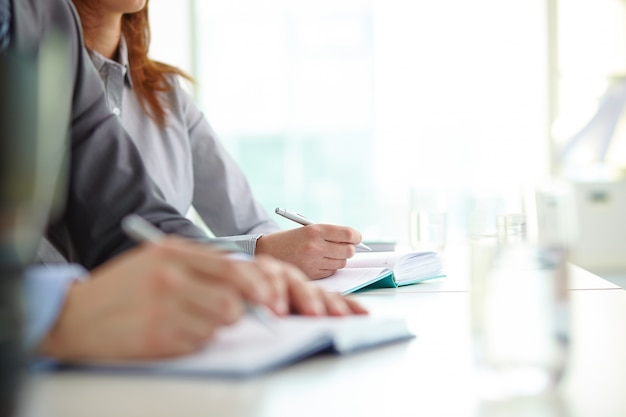 Manos en primer plano de compañeros de trabajo escribiendo