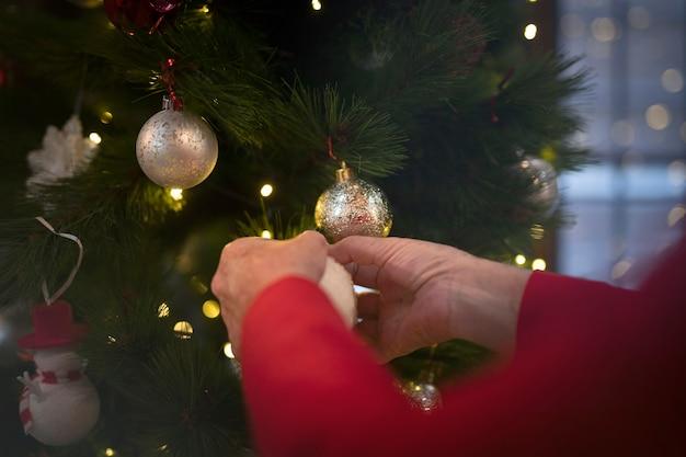Manos de primer plano configurando el árbol de navidad