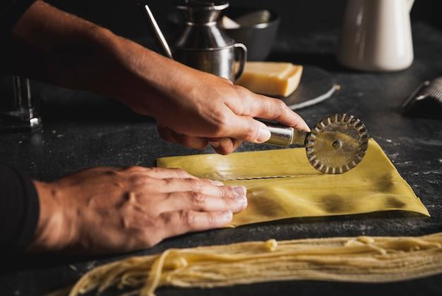 Manos de primer plano con cortador de pizza y utensilios