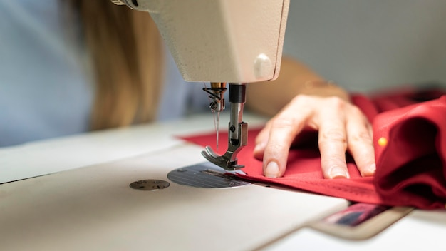 Manos de primer plano coser con máquina