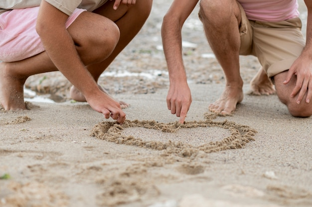 Manos de primer plano dibujo corazón sobre arena.