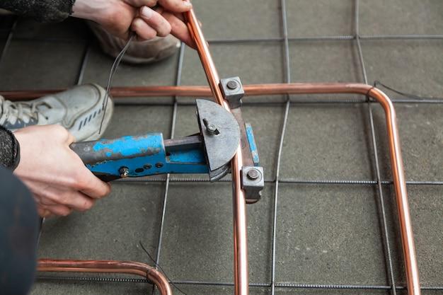 Manos de primer plano dobla tubos de cobre por doblador de tubos