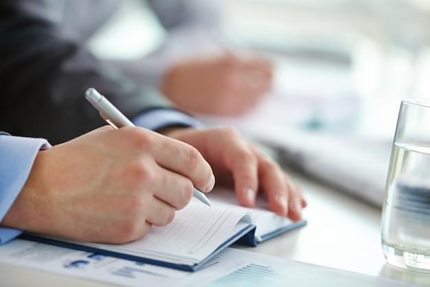 Manos en primer plano de ejecutivo escribiendo una carta