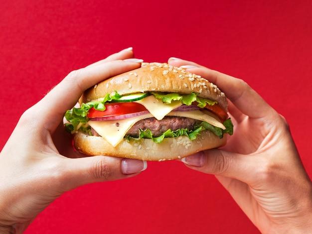 Manos de primer plano con gran hamburguesa con queso