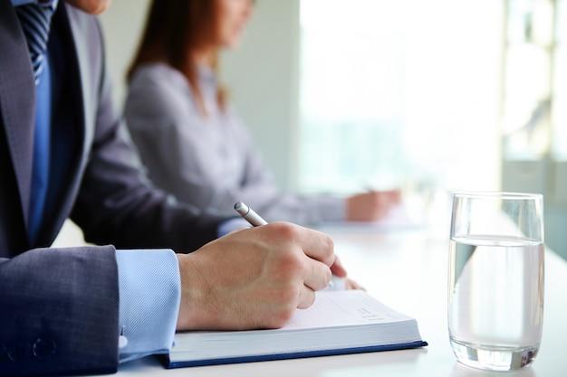 Manos en primer plano de hombre escribiendo en su agenda