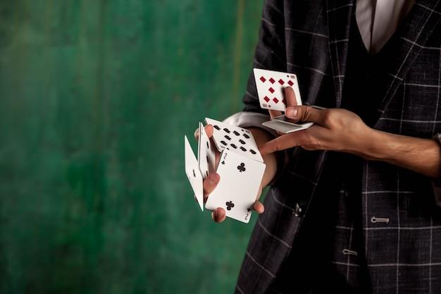 Manos de primer plano de joven con cartas de juego. chico guapo muestra trucos con tarjeta. manos inteligentes de mago