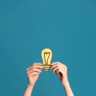 Manos de primer plano con luz de idea con espacio de copia
