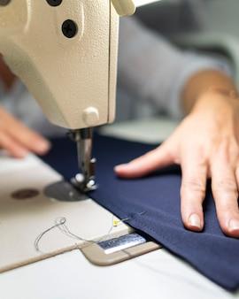Manos de primer plano con máquina de coser