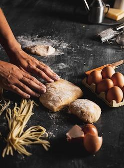 Manos de primer plano con masa y huevos