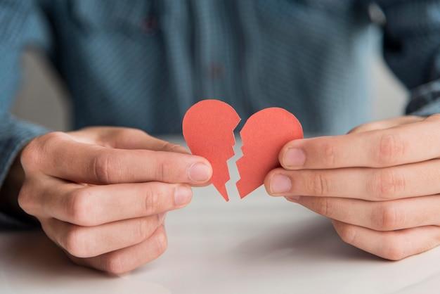 Manos de primer plano con piezas de corazón