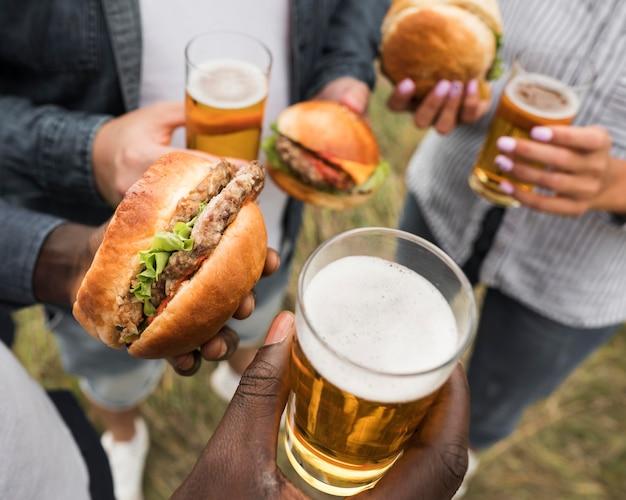 Manos de primer plano sosteniendo alimentos y bebidas