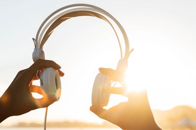 Manos de primer plano sosteniendo auriculares