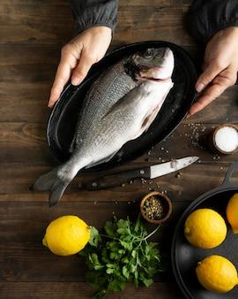Manos de primer plano sosteniendo la bandeja con pescado