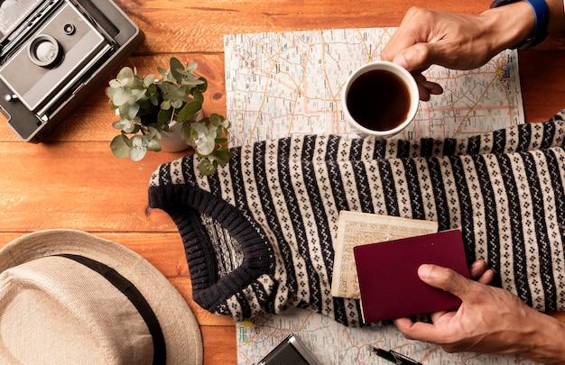 Manos de primer plano sosteniendo café y pasaporte