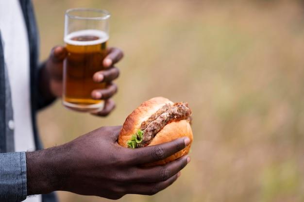 Manos de primer plano sosteniendo cerveza y hamburguesa