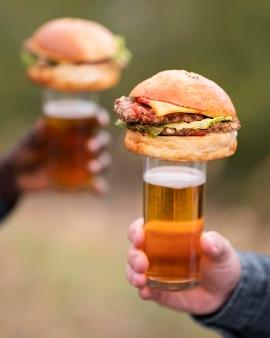 Manos de primer plano sosteniendo cerveza y hamburguesas