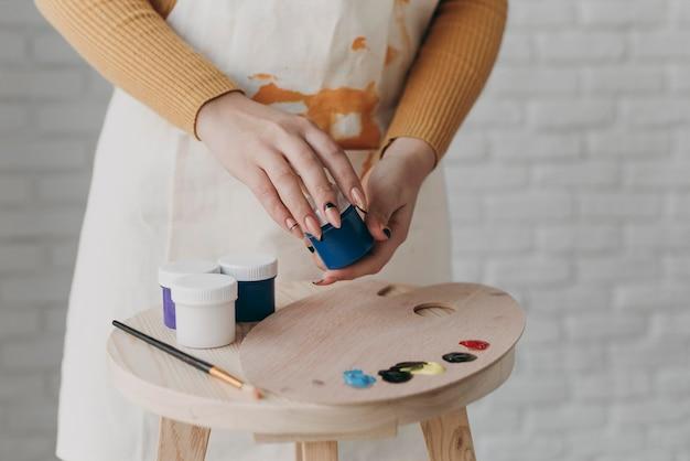 Manos de primer plano sosteniendo el contenedor de pintura