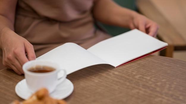 Manos de primer plano sosteniendo el cuaderno