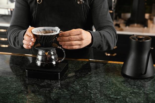 Manos de primer plano sosteniendo el filtro de café