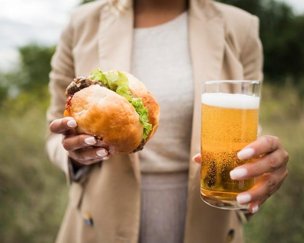 Manos de primer plano sosteniendo hamburguesa y cerveza