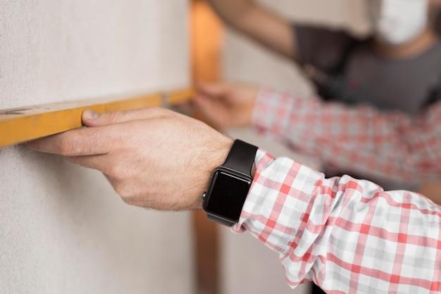 Manos de primer plano sosteniendo la herramienta de medición