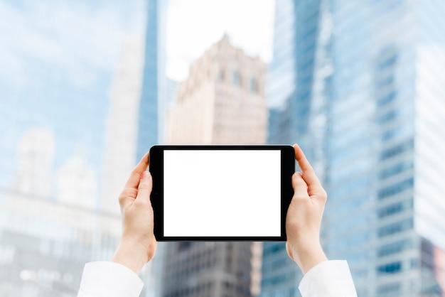 Manos de primer plano sosteniendo una maqueta de tableta