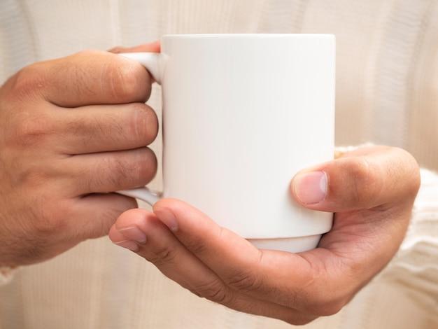 Manos de primer plano sosteniendo una maqueta de taza