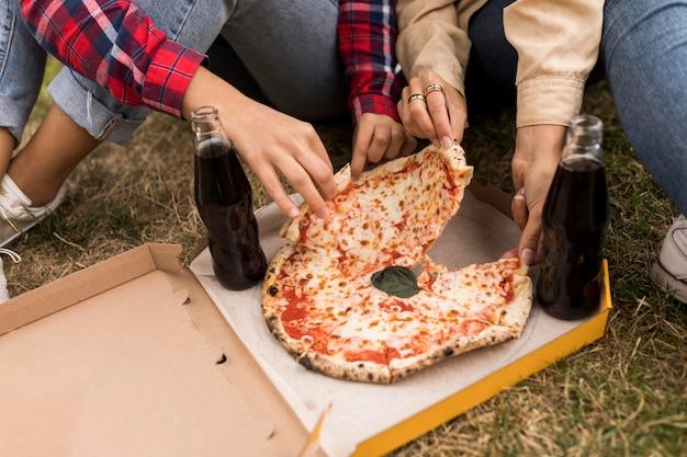 Manos de primer plano sosteniendo pizza