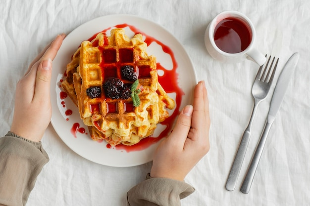 Manos de primer plano sosteniendo el plato con waffles