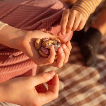 Manos de primer plano sosteniendo sabrosas galletas